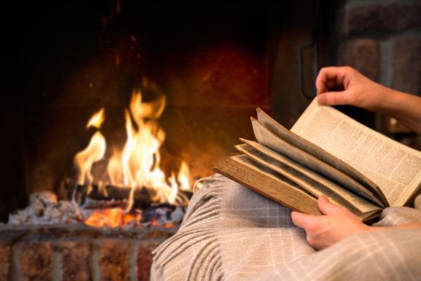 Antiquariat - Person liest vor dem Lagerfeuer