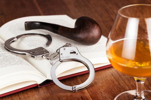 Krimi - Buch, Handschellen, Pfeife und Cognac auf Holztisch
